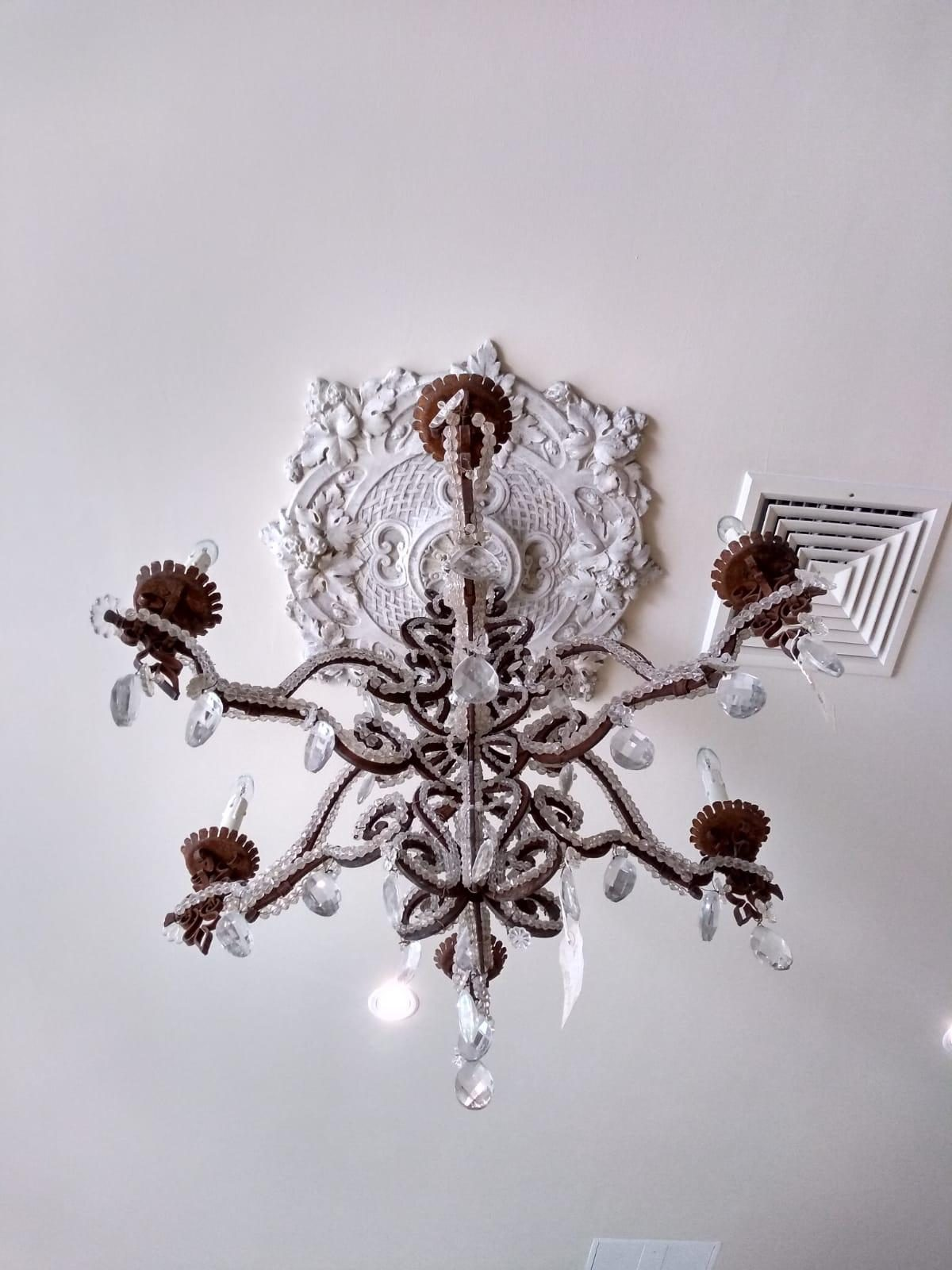 A vintage chandelier and antique ceiling rose